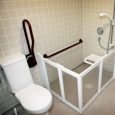 A shower adaption with handrails and seat