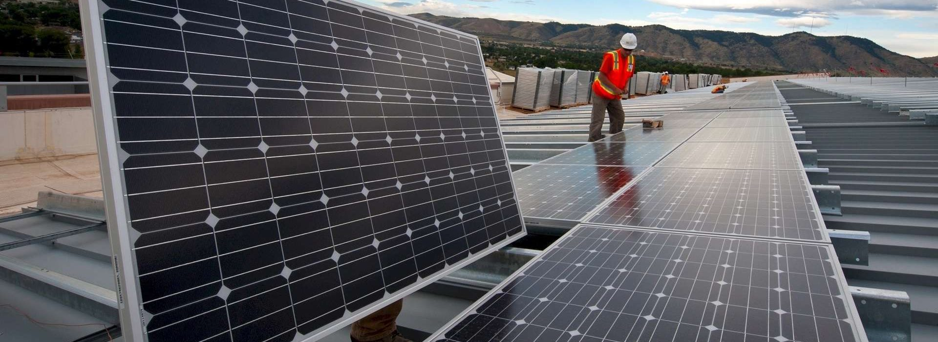 Two men fitting solar panels on a large roof as part of sustainable energy